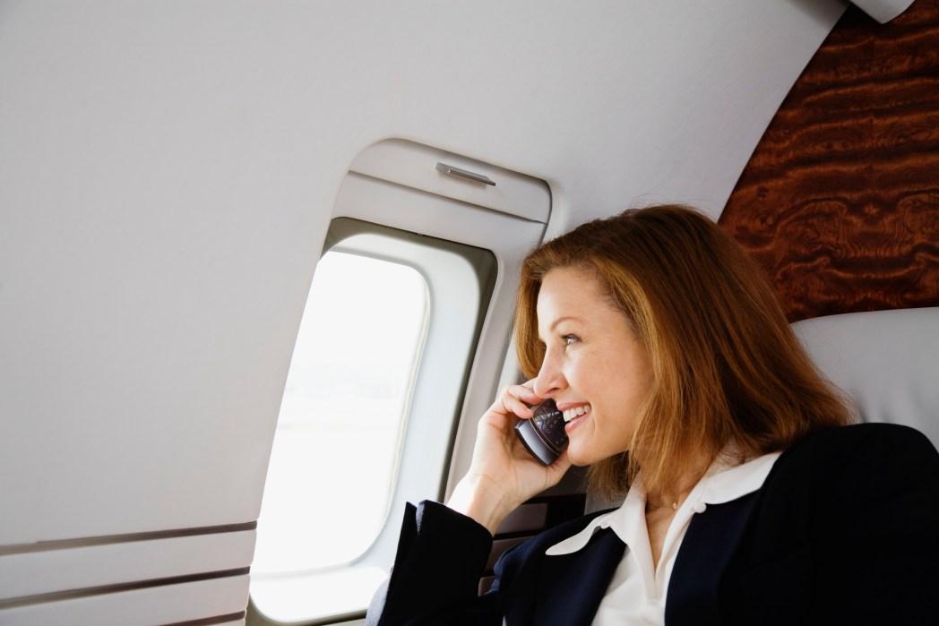 Dame snakker i telefonen ombord på fly